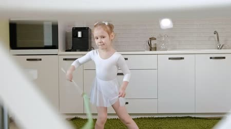 aerobic : A happy little girl in a white gymnastic swimsuit trains, dances with a ribbon for rhythmic gymnastics, jumps and performing professional exercises. Wideo