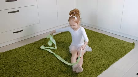 ritmische gymnastiek : A happy little girl in a white gymnastic swimsuit trains, dances with a ribbon for rhythmic gymnastics, jumps and performing professional exercises. Stockvideo
