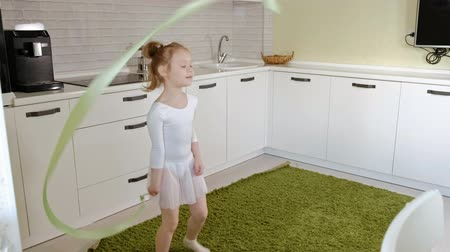 rhythmic : A happy little girl in a white gymnastic swimsuit trains, dances with a ribbon for rhythmic gymnastics, jumps and performing professional exercises. Stock Footage