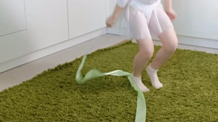 leaping : A happy little girl in a white gymnastic swimsuit trains, dances with a ribbon for rhythmic gymnastics, jumps and performing professional exercises. Stock Footage