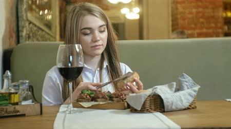 pasztet : Beautiful blonde woman eating and drinking in restaurant, lunch break Wideo