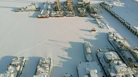прерыватель : Large river ships in the winter parking lot. The ships are frozen in the ice. Aerial filming