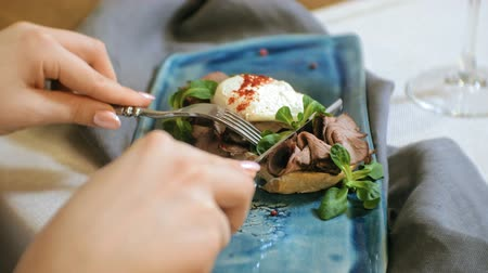 poached egg : close-up shooting: a delicious sandwich with beef, poached egg and lettuce leaves,bruschetta.