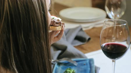 bruschetta : Beautiful blonde woman eating and drinking in restaurant, lunch break Stock Footage