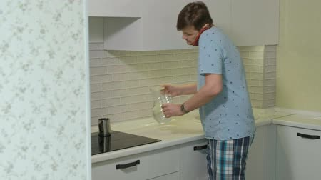 bastião : A man in pajamas drinking water in the kitchen. Morning Stock Footage