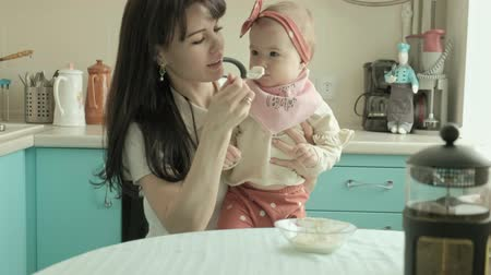 oturur : Mother feeds the baby with a spoon. Mother concept Stok Video