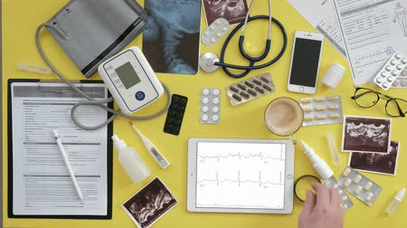 drinking coffee : Top view of the therapists desktop, ECG results on a computer tablet, ultrasound, medicine and health care concept Stock Footage