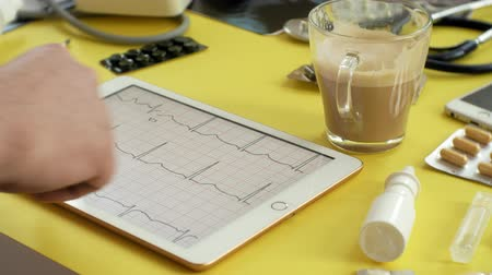 magnifier : Side view of the therapists desktop, ECG results on a computer tablet, ultrasound, medicine and health care concept Stock Footage