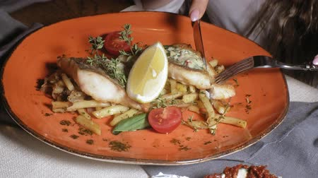 cuisine dark : close-up shooting: baked salmon with spices, french fries and a slice of lemon on an orange plate Stock Footage
