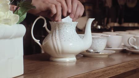 elegancia : A man pours tea from a kettle into a white cup on a wooden table.