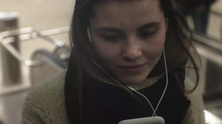 construído : young brunette woman uses a phone with headphones