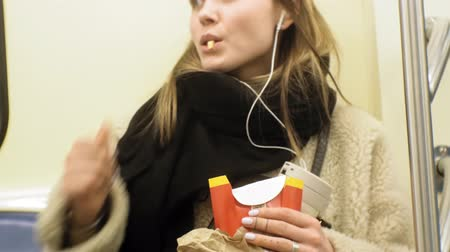 french media : young brunette woman rides on public transport, uses the phone with headphones