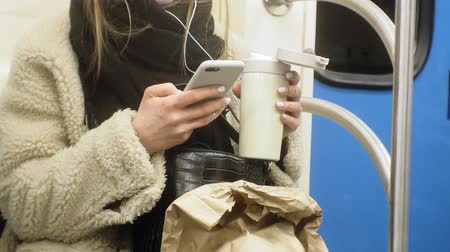 fastfood : young brunette woman rides on public transport, uses the phone with headphones
