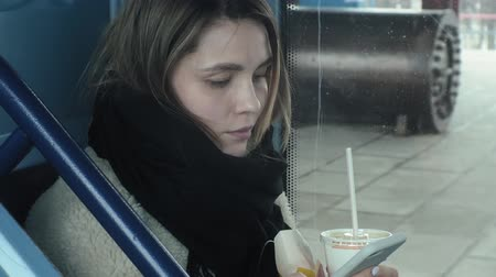 フライドポテト : young brunette woman rides on public transport, uses the phone with headphones