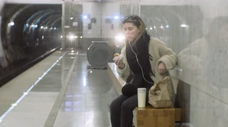train tunnel : woman eating fast food in the subway