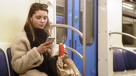 evez : young brunette woman rides on public transport, uses the phone with headphones