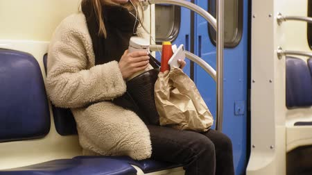 batatas fritas : young brunette woman rides on public transport, uses the phone with headphones