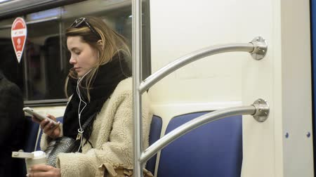 autobus : young brunette woman rides on public transport, uses the phone with headphones