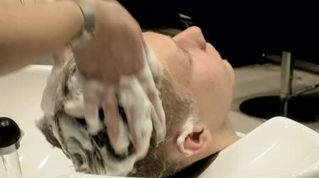 szampon : hairdresser washes the head boy in the salon