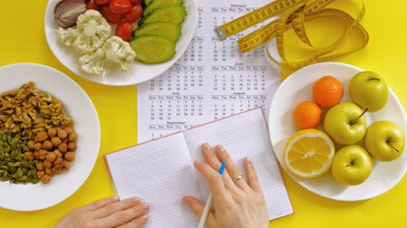 there : sports calendar, healthy food, shooting on a yellow background top view