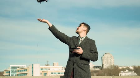 takes : man controls quadcopter outdoors