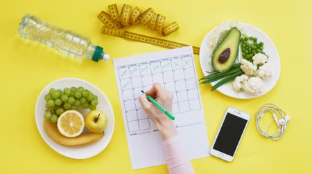 sida : Keeping a fitness calendar.concept of healthy food, diet, top view, yellow background