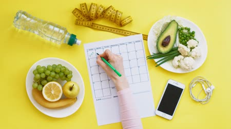 beginnings : Keeping a fitness calendar.concept of healthy food, diet, top view, yellow background