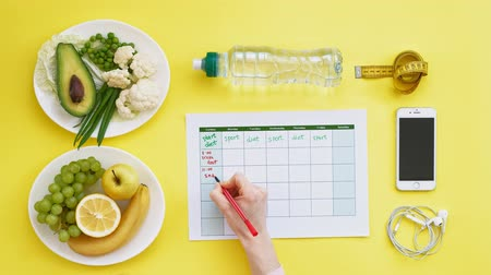 устроенный : Keeping a fitness calendar.concept of healthy food, diet, top view, yellow background