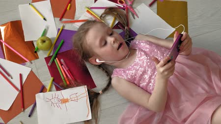 zene : little girl lying on the floor uses the phone, listens to music Stock mozgókép