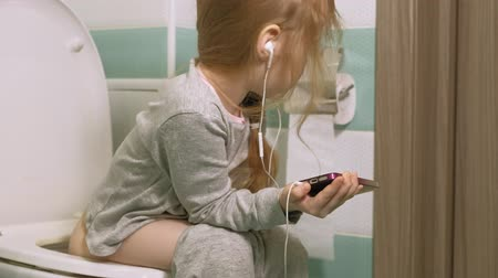 toilet paper : little girl sits on the toilet and uses the phone