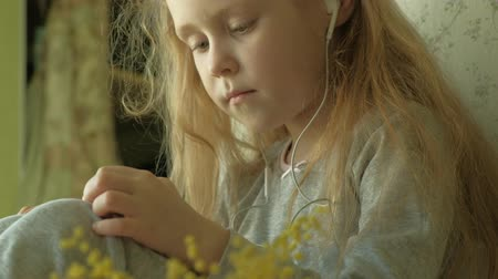 tüy : little girl sitting on the window uses the phone Stok Video