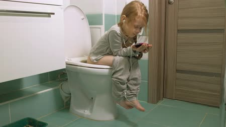 uses : little girl sits on the toilet and uses the phone