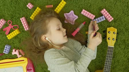 pink background : little girl lying on a green background in headphones and using a phone, top view