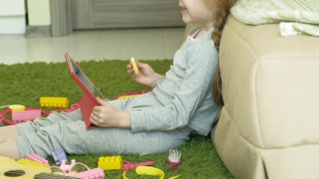 pizsama : little girl uses a computer tablet in the interior Stock mozgókép