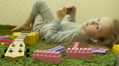 ileri : little girl lying on a green background in headphones and using a phone, top view