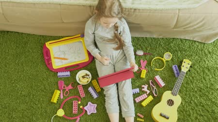 sitting floor : little girl uses a computer tablet in the interior Stock Footage