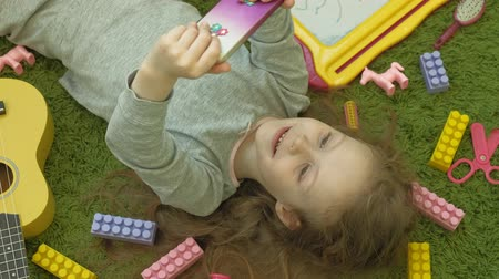 plaything : little girl lying on a green background in headphones and using a phone, top view