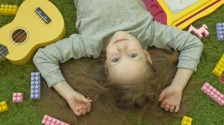 ileri : little girl laughs lying on green background, top view Stok Video
