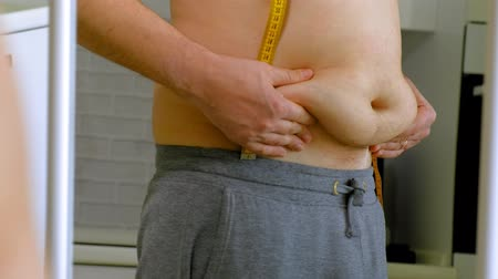 bel ölçüsü : fat man measuring his waist, healthy eating, healthy lifestyle concept, fitness diet