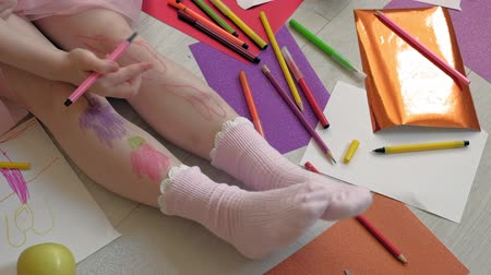 crayon : little girl draws on her feet with felt-tip pens, childrens creativity, development