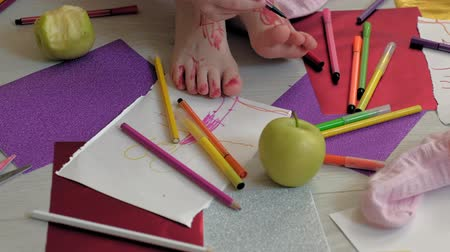 sheet : little girl draws on her feet with felt-tip pens, childrens creativity, development
