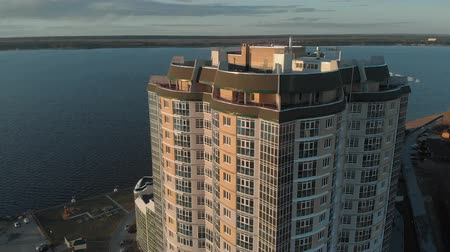 komplexní : Cityscape. Residential complex on the river bank. Aerial footage from a copter at sunset time