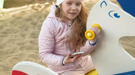 trenzas : little girl riding a swing and using a phone with headphones Archivo de Video