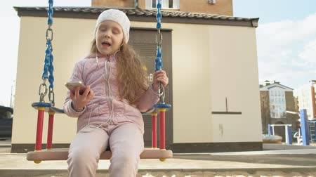 warkocz : little girl riding a swing and using a phone with headphones Wideo