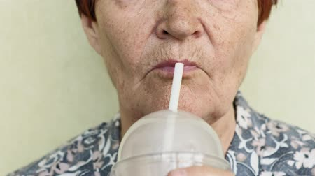 turmix : old woman drinking a drink from a straw closeup