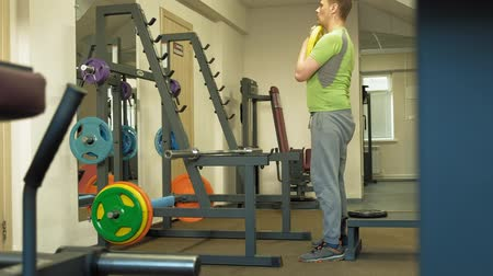 atlet : The overweight man does squats with squats with a weight disc for a barbell. Fitness training. Healthy lifestyle concept Stok Video