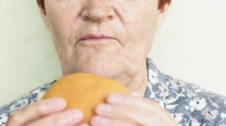 olgun : old woman eating burger closeup, fast food Stok Video