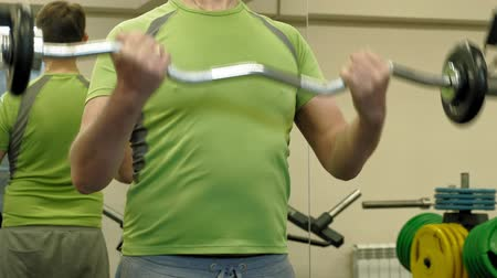кулак : A overweight man lifts an ez barbell while standing at the gym. Exercise for biceps. Fitness. Healthy lifestyle.