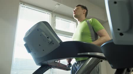 his : A overweight man on a treadmill in a gym. Fitness. Healthy lifestyle
