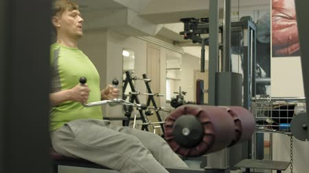 borotválatlan : The overweight man shares lower cravings, back exercises, in the gym. Fitness. Healthy lifestyle